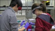 A male and female student with goggles on stand at a lab bench handling test tubes.
