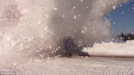 The person videoing the action is showered with a huge snow cloud as the train crashes past